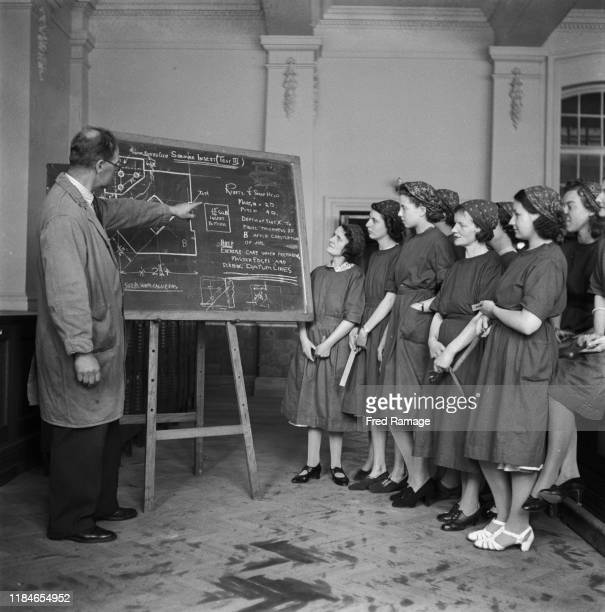 Women learn about the use of rivets during a class at the Chiswick Polytechnic in Turnham Green, London during World War II, June 1941. From a...
