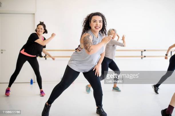 women learning dance in a fitness class - fat lady in leggings stock photos and pictures