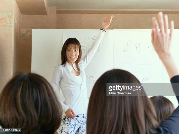 women learning new knowledge from professional instructors - free business coaching stock pictures, royalty-free photos & images