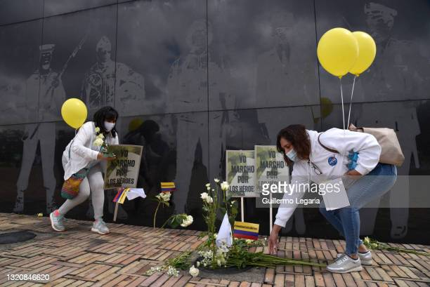 Women leave white flowers at the memorial to fallen soldiers and police officers as they take part in a movilization against blockades and violence...