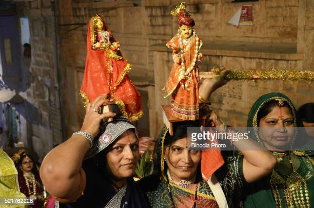 women lifting idol of gangaur and isar on head in jodhpur at rajasthan, india - gangaur stock pictures, royalty-free photos & images