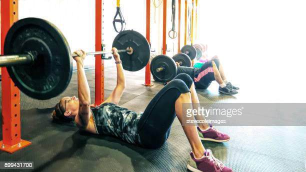 Women lifting weight with barbell.