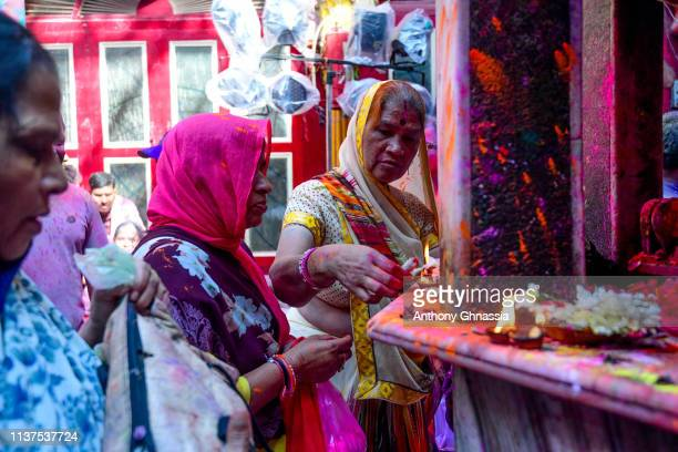 Women light candles during the celebration of the Holi Festival on March 21 2019 in Mathura India