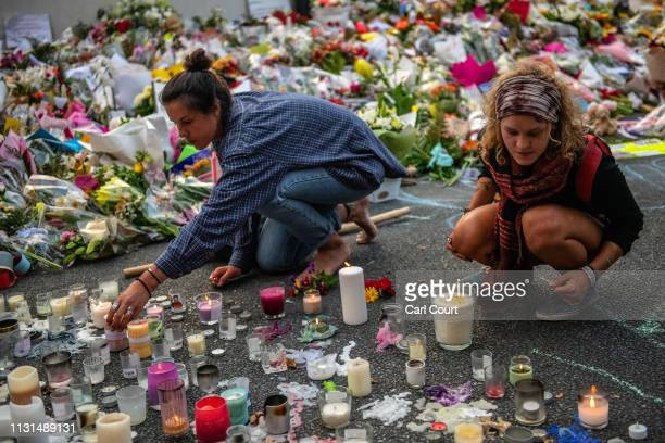 Women light candles next to flowers and tributes near Al Noor mosque on March 19 2019 in Christchurch New Zealand 50 people were killed and dozens...