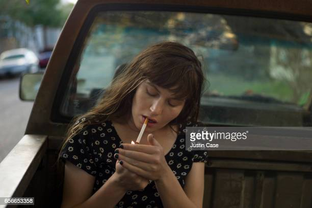 women lighting a cigarette on the back of her pick up truck - beautiful women smoking cigarettes stock pictures, royalty-free photos & images