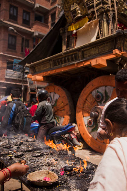 Women lighting butter lamps at the base of an ornate chariot celebrating the Bunga Dyo Jatra Festival in Patan, Kathmandu, Nepal.