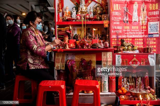 """Women lights a candle as she waits for customers in a """"villain hitting"""" ritual in the Causeway Bay district of Hong Kong on March 5, 2020. - Villian..."""