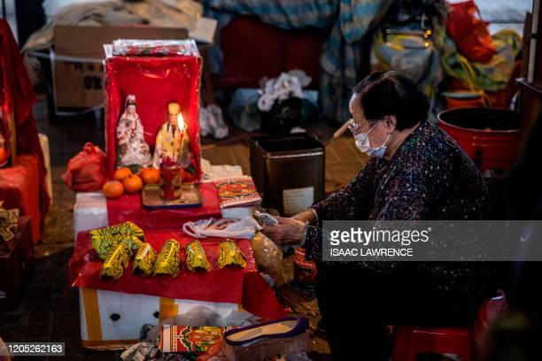 "Women lights a candle as she waits for customers in a ""villain hitting"" ritual in the Causeway Bay district of Hong Kong on March 5, 2020. - Villian..."