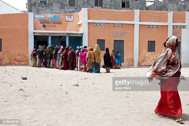 Women line on a Mogadishu street waiting for food handouts from a feeding center Thousands of people in Mogadishu rely on free food kitchens to be...