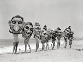 Women lined up on a beach hold giant masks in front of their faces picture id517323260?s=170x170