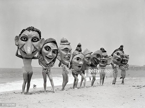 Women lined up on a beach hold giant masks in front of their faces which will be featured in the annual Venice Mardi Gras celebration