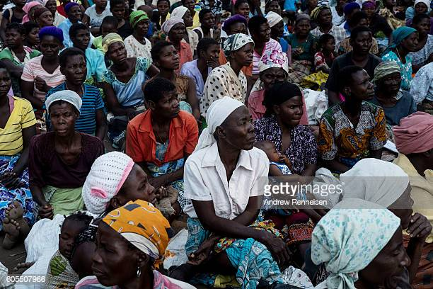 Women listen to a briefing on the food distribution process outside a school in the village of Malikopo which lies in one of the areas most affected...
