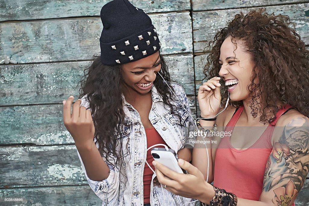 Women listening to mp3 player on city street : Stock Photo
