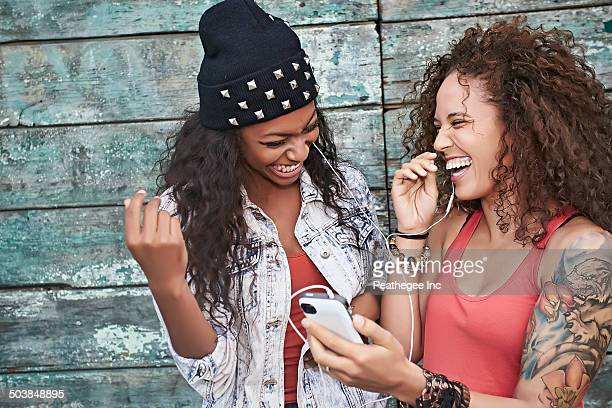 women listening to mp3 player on city street - black people laughing stock photos and pictures