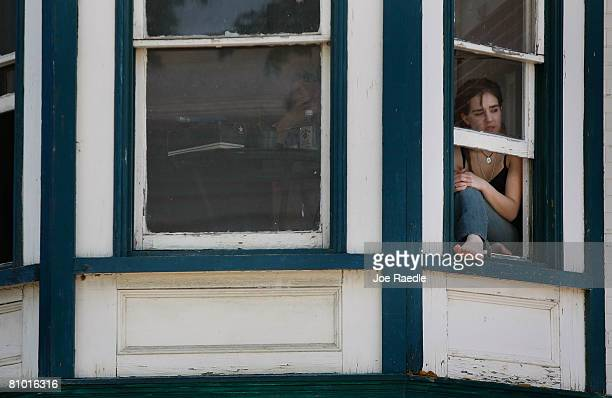 A women listens from her window as Democratic presidential hopeful US Senator Hillary Clinton speaks during a campaign event at Shepherd University...