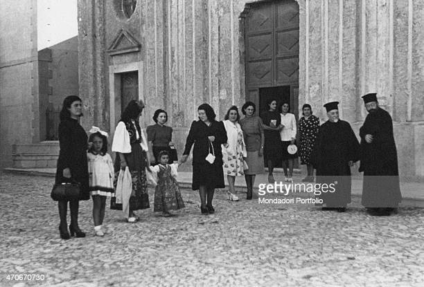 'Women little girls and Eastern Christian priests members of the Arbereshe community standing in front of the church of the Santissima Annunziata...