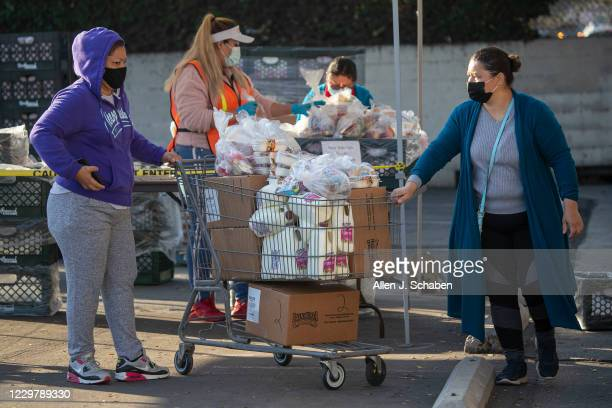 Women load up a shopping cart of free meals after waiting in a long line of people walking in, which was in addition to a line of cars that wrapped...