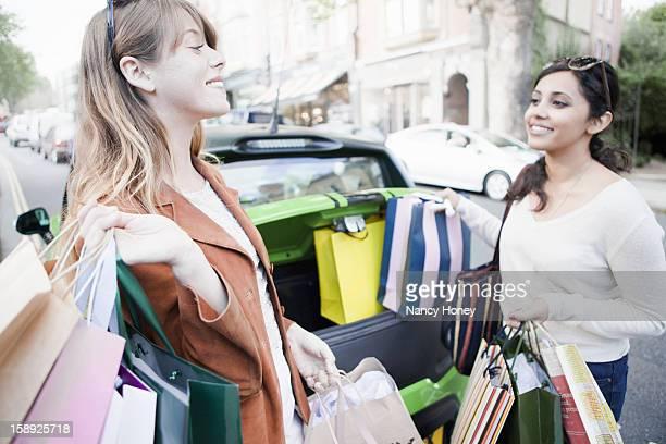 Women loading shopping bags in car