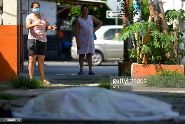 Women look at a body said to be laying for three days outside a closed clinic in Guayaquil Ecuador on April 3 2020 Troops and police in Ecuador have...