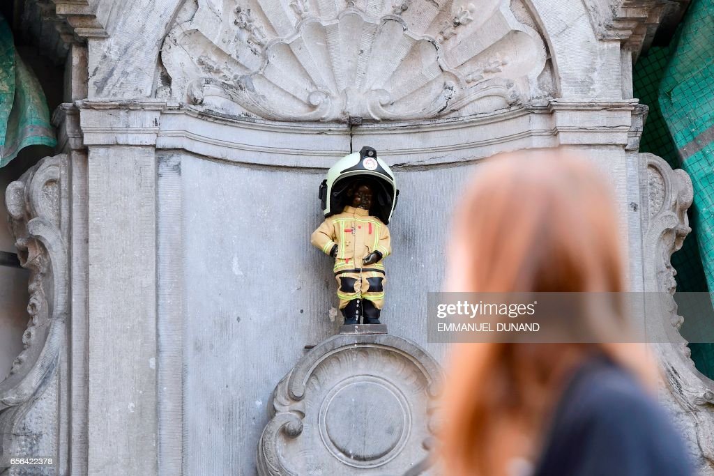 TOPSHOT - Women look at Brussels' most famous landmark -- the Manneken Pis statue of a little boy -- is dressed up in a fireman's outfit to hail the efforts of rescue services as Belgium commemorates the victims of last year's terrorist attacks on March 22, 2017. Belgium marks the first anniversary of the Islamic State bombings in Brussels, one at the airport and the other in the metro, in which 32 people were killed and more than 320 wounded with ceremonies showing that the heart of Europe stands defiant. / AFP PHOTO / BELGA AND AFP PHOTO / Emmanuel DUNAND