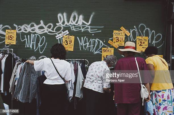Women look at clothes at an outdoor stall in the East Village Manhattan New York City USA June 1982