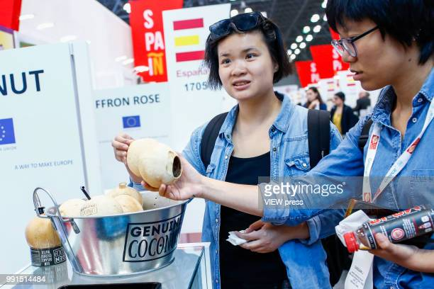women look at coconuts during The Summer Fancy Food Show at the Javits Center in the borough of Manhattan on July 02 2018 in New York The Summer...