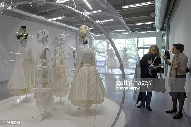 Women look at creations by Japanese designer Rei Kawakubo for Comme des Garçons fashion house exhibited at the Cité de la Mode on April 11 2012 in...