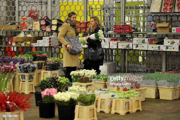 women look at flowers on a market stall on December 16 2013 in London England New Covent Garden Flower Market is London's premier wholesale market...