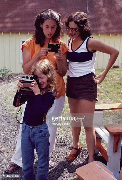 Women look at photographs while a girl takes pictures with a Kodak instant camera 1979