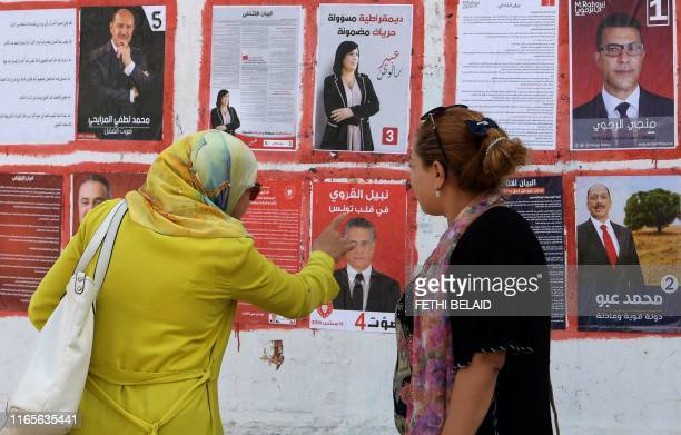 Women look at posters of Tunisian presidential candidates in the capital Tunis on September 2 2019 Campaigning for Tunisia's presidential elections...