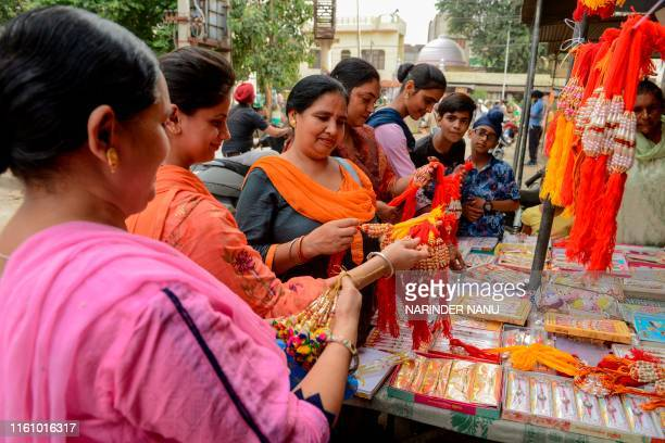 Women look at 'rakhis' ahead of the annual Hindu festival 'Raksha Bandhan' that is celebrated with a ritual of tying a string or bracelet to...