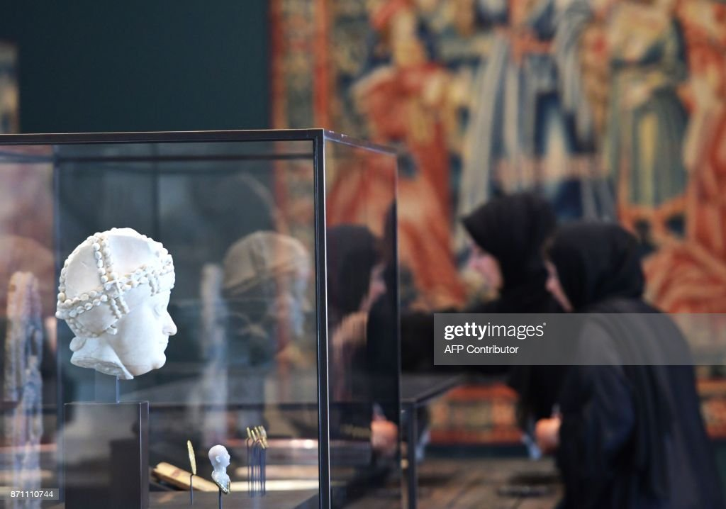 Women look at statues on display in a gallery at the Louvre Abu Dhabi Museum during a media tour on November 6, 2017 prior to the official opening of the museum on Saadiyat island in the Emirati capital on November 8. More than a decade in the making, the Louvre Abu Dhabi opens its doors this week, bringing the famed name to the Arab world for the first time. The museum currently has some 300 pieces on loan, including an 1887 self-portrait by Vincent van Gogh and Leonardo da Vinci's 'La Belle Ferronniere'. /