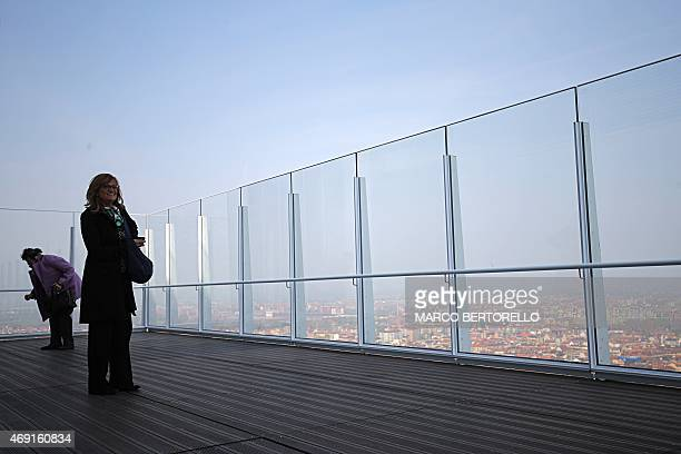 Women look at the city from a terrace during the inauguration of the Intesa Sanpaolo tower head office of the bank on April 10 2015 in Turin The166...