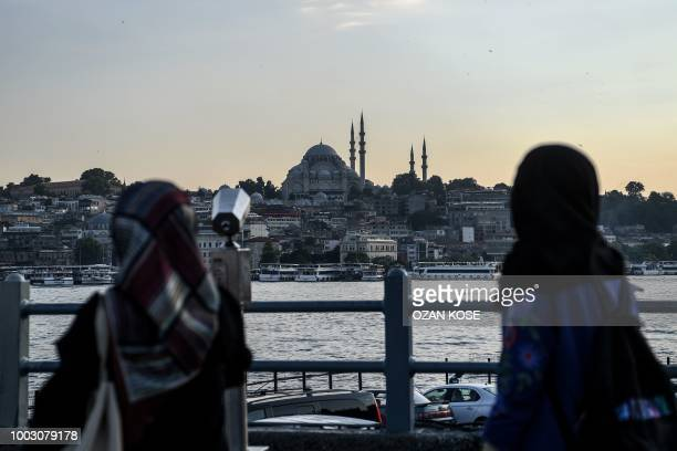 Women look at the Suleymaniye mosque from the Galata Bridge in the disctrict of Eminonu in Istanbul on July 21 2018