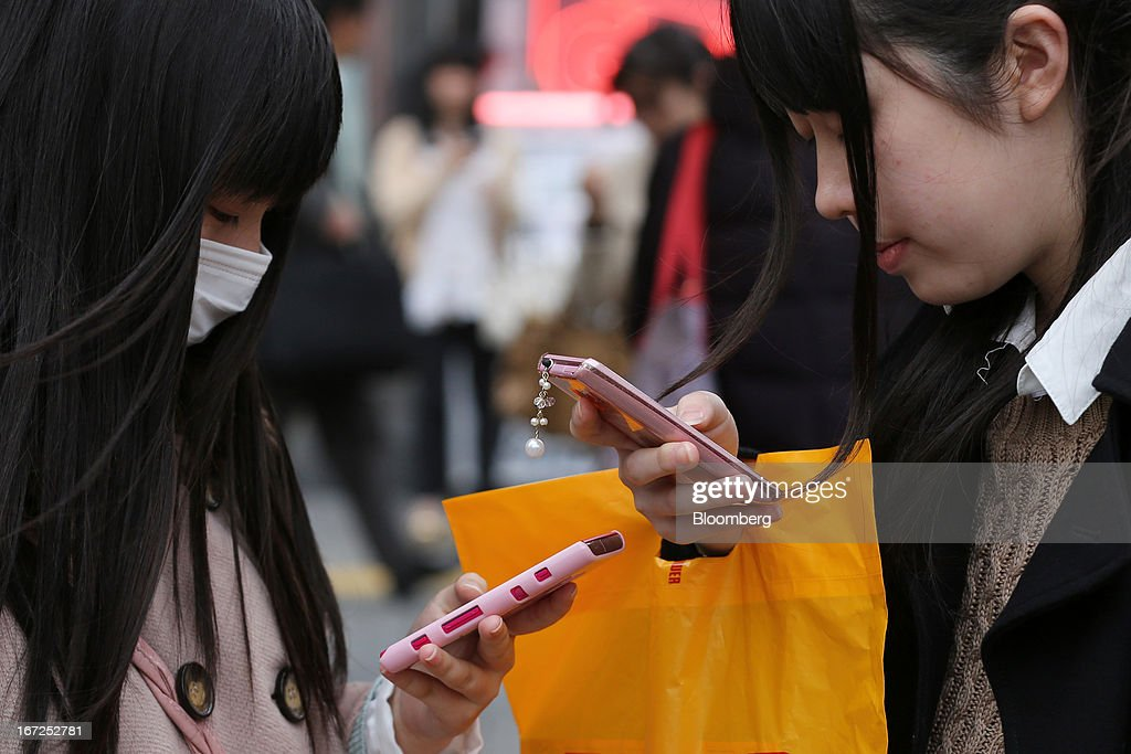 Women look at their smartphones in Tokyo, Japan, on Sunday, April 21, 2013. The number of smartphone subscribers in Japan surged to 37 percent of all contracts as of March 31 from 3 percent three years earlier, according to Tokyo-based MM Research Institute Ltd. Photographer: Yuriko Nakao/Bloomberg via Getty Images