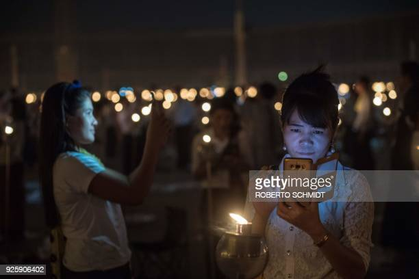 Women look into their mobiles during Makha Bucha Day celebrations at Wat Phra Dhammakaya temple near Bangkok on March 1 2018 Makha Bucha Day is held...
