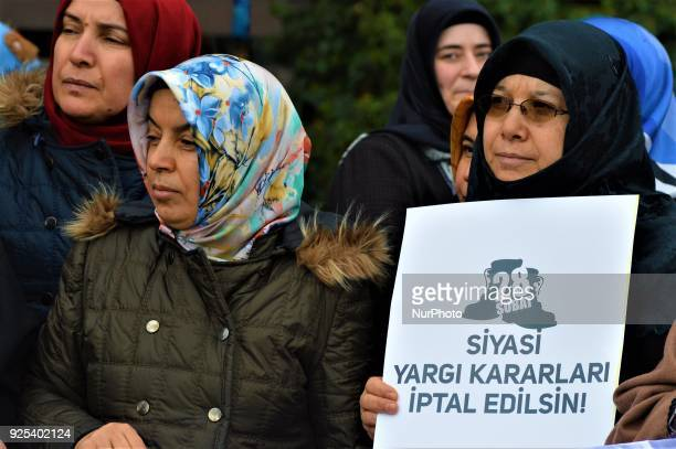 Women look on as an organized group of proIslamic demonstrators makes a statement outside the main courthouse on the 21th anniversary of Turkey's...