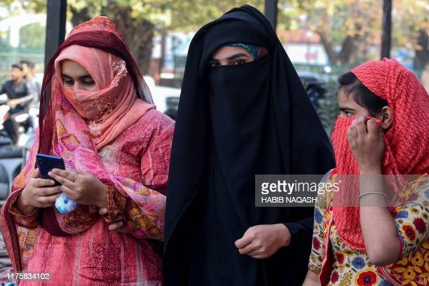 Women look on as they use mobiles phones in Srinagar on October 14 following Indian government's decision to restore mobile phones network in...