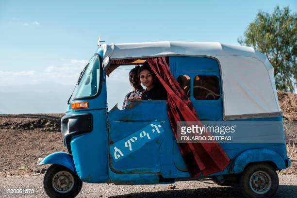 Women look on from inside a tuk-tuk in the village of Chercher, east of the Ethiopian city of Alamata, on December 10, 2020. - The village of...