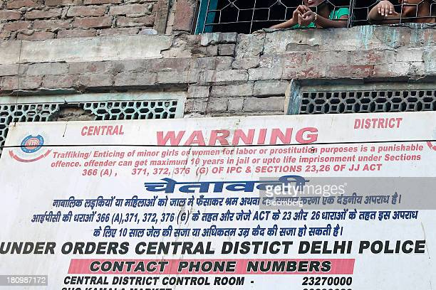 Women look out the window of a building above signage warning of the penalties for trafficking minor girls on Garstin Bastion Road in New Delhi India...