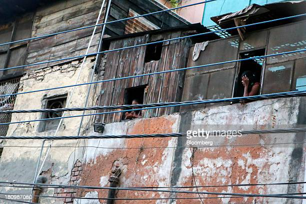 Women look out the windows of a building on Garstin Bastion Road in New Delhi India on Wednesday Sept 18 2013 Districts such as Bharatpur Rajastan...
