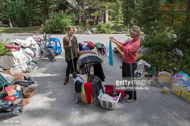 women look over belongings at garage sale,driveway - venta de garaje fotografías e imágenes de stock
