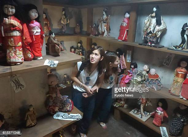 Women look scared in a mazelike horror attraction featuring many Japanese dolls at the Universal Studios Japan theme park in Osaka which started Sept...