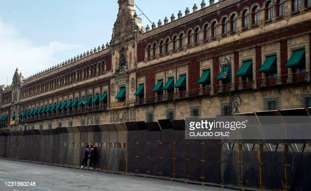 Women look through a metal fence surrounding the National Palace placed as a preventive measure against possible marches ahead of the International...