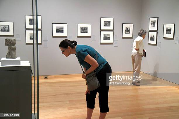 Women looking at a sculpture and black and white photos in the Museum of Fine Arts