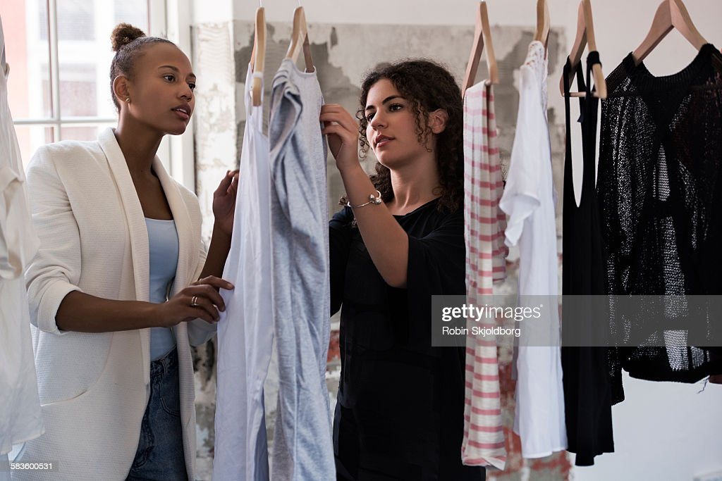 Women looking at clothes on rack : Stock Photo
