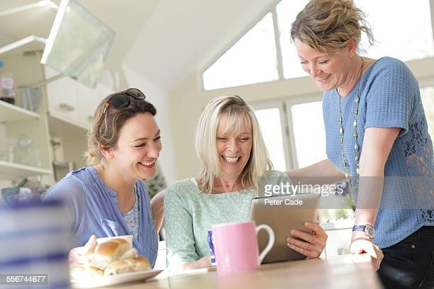 women looking at computer tablet laughing .