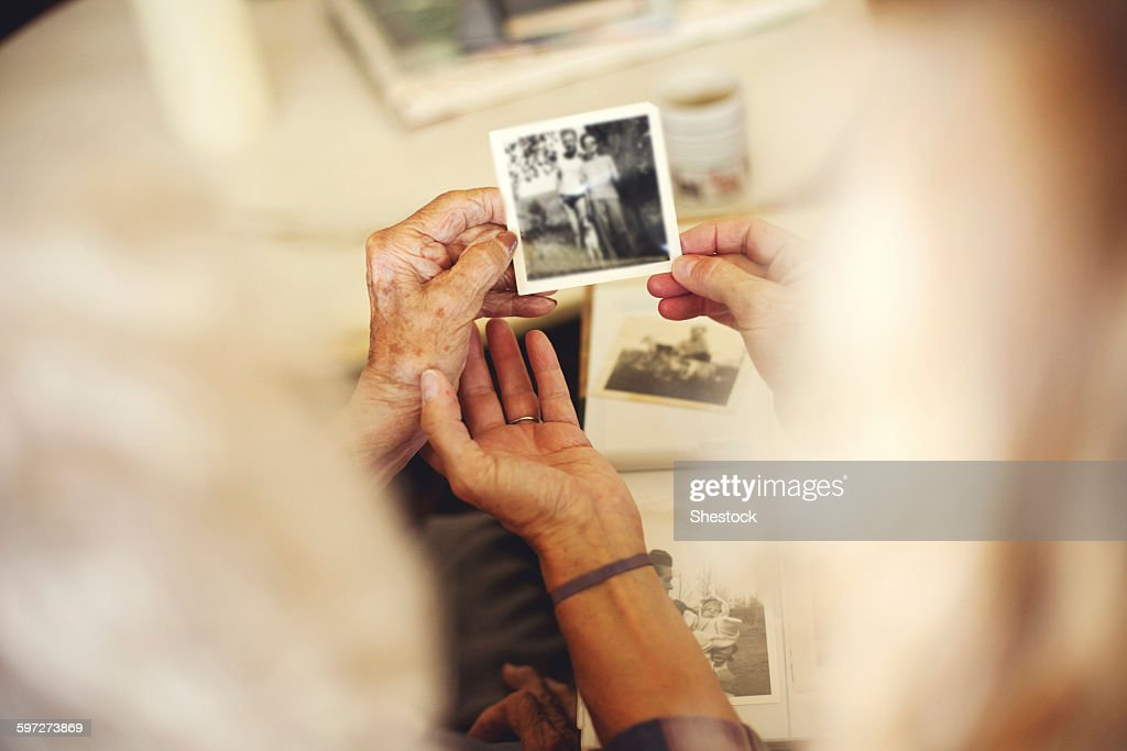 Women looking at family photographs : Stock Photo