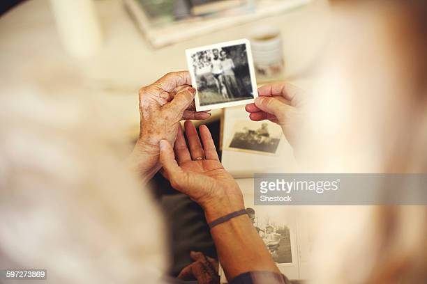 women looking at family photographs - ricordi foto e immagini stock
