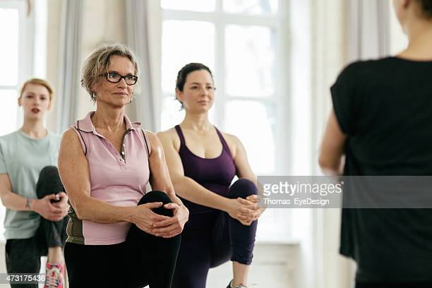 women looking at instructor while exercising in gym - knees together stock photos and pictures